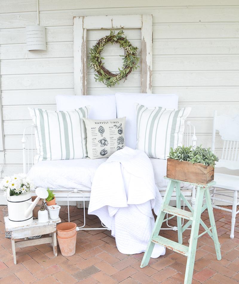 A cozy vintage cribe on the back patio. Farmhouse style summer patio idea!