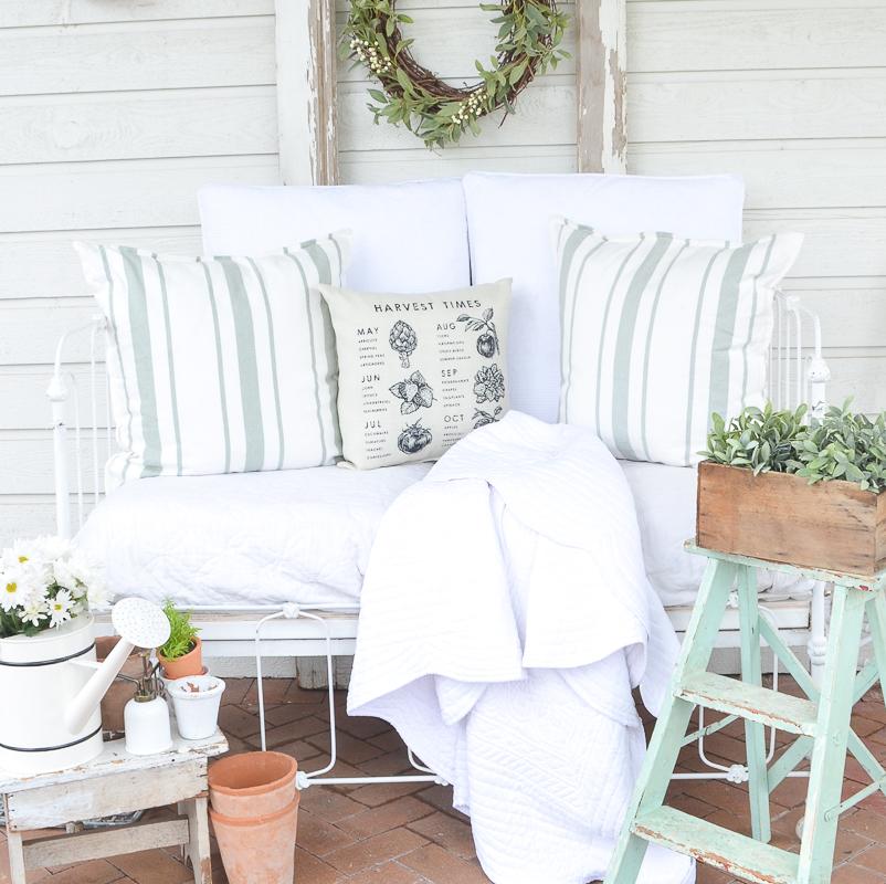 A cozy vintage crib on the back patio for summer. Farmhouse style summer patio idea!