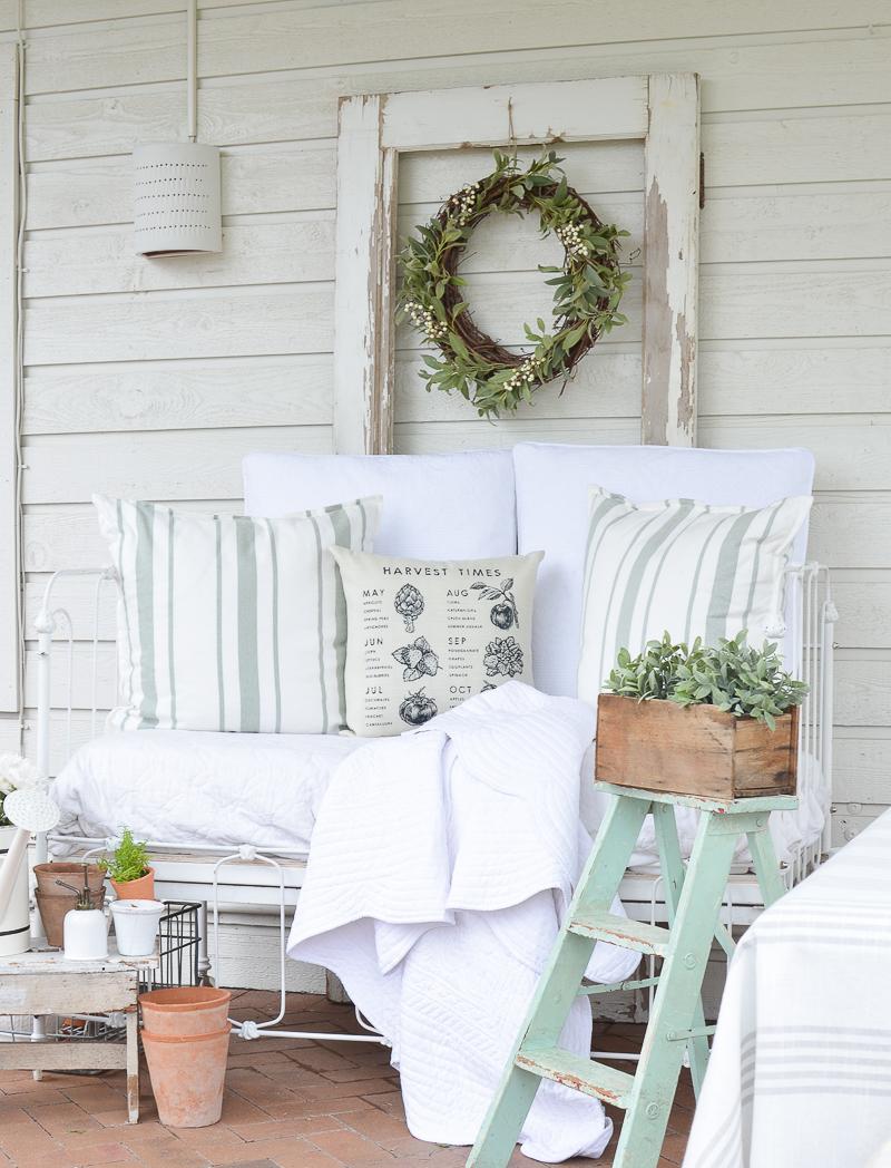 A Cozy Vintage Crib on the Back Patio. Farmhouse style summer patio idea with a vintage crib!