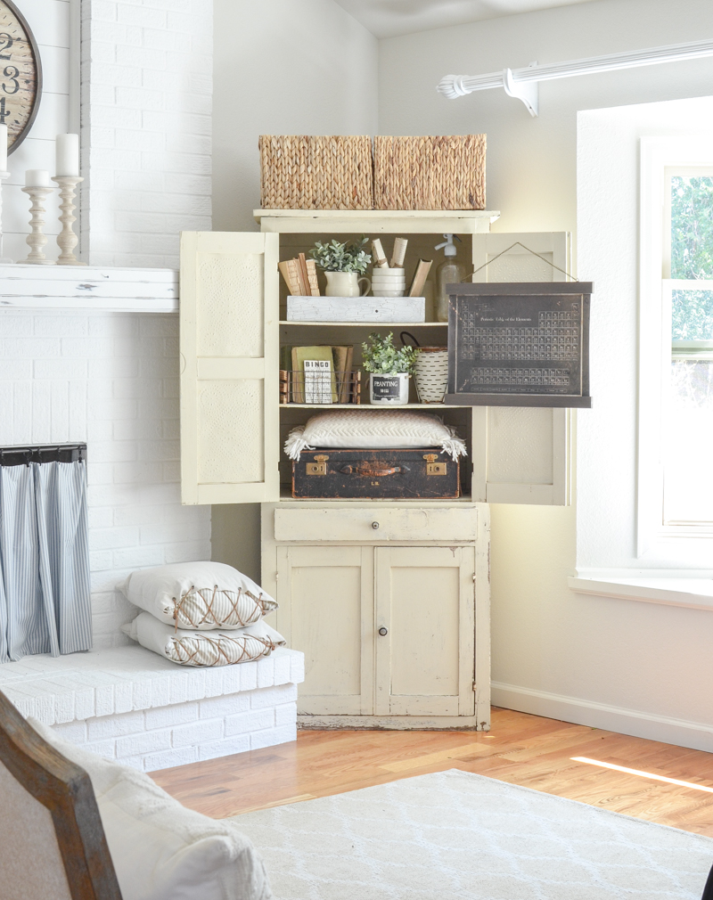 Farmhouse style decor in an antique cabinet. Living room inspiration!